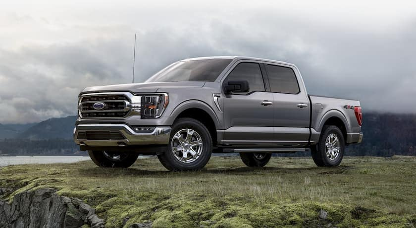 A grey 2021 Ford F-150 is parked on grass with misty hills in the distance.