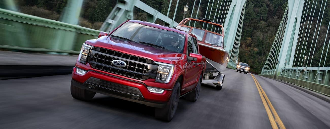 A red 2021 Ford F-150 is towing a boat over a green bridge near Cincinnati, OH.