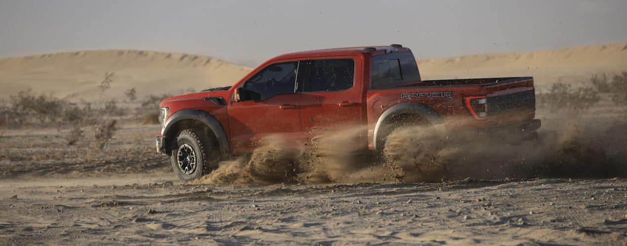 A red 2021 Ford F-150 Raptor is off-roading in dirt.