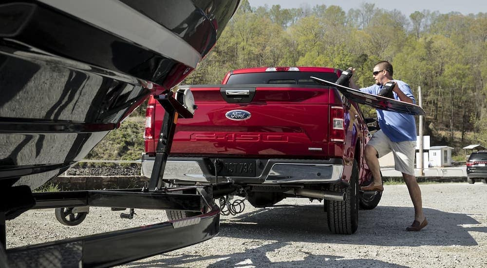 A man is loading a wakeboard into a red 2020 Ford F-150 which has a boat and trailer attached, shown from the rear.