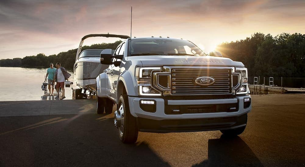 A popular Ford truck for sale in Cincinnati, a white 2020 Ford Super Duty is towing a boat from a loading ramp at sunset, shown from the front.