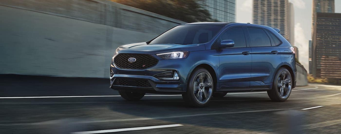 A blue Ford Edge is racing around a street corner after winning the 2020 Ford Edge vs 2020 Nissan Murano comparison.