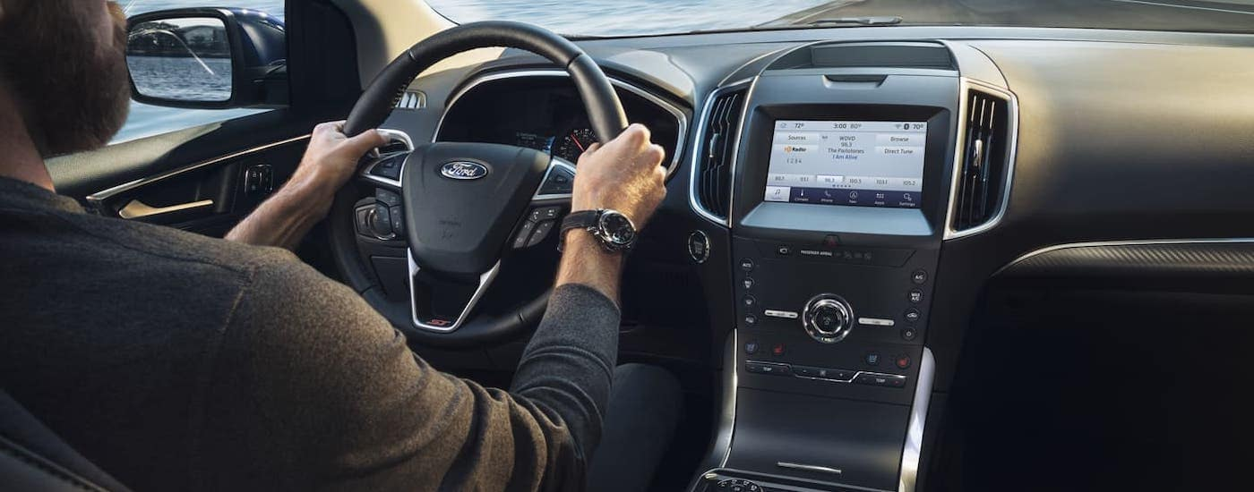 The interior and dashboard of a 2020 Ford Edge is shown while being driven down a road.
