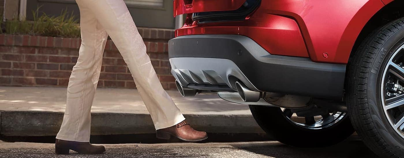 A foot is using the automatic liftgate feature on a red 2020 Ford Edge.