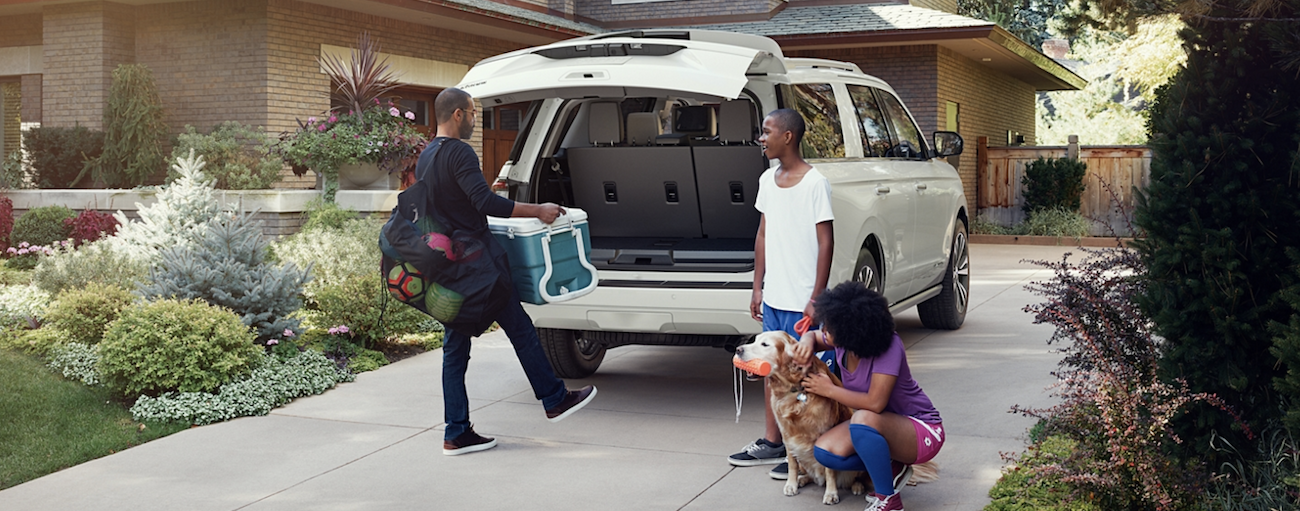 A family is loading sports gear into a white 2020 Ford Expedition in their driveway.