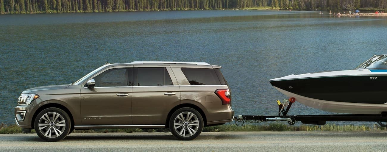 A tan 2020 Ford Expedition is towing a boat past a lake.