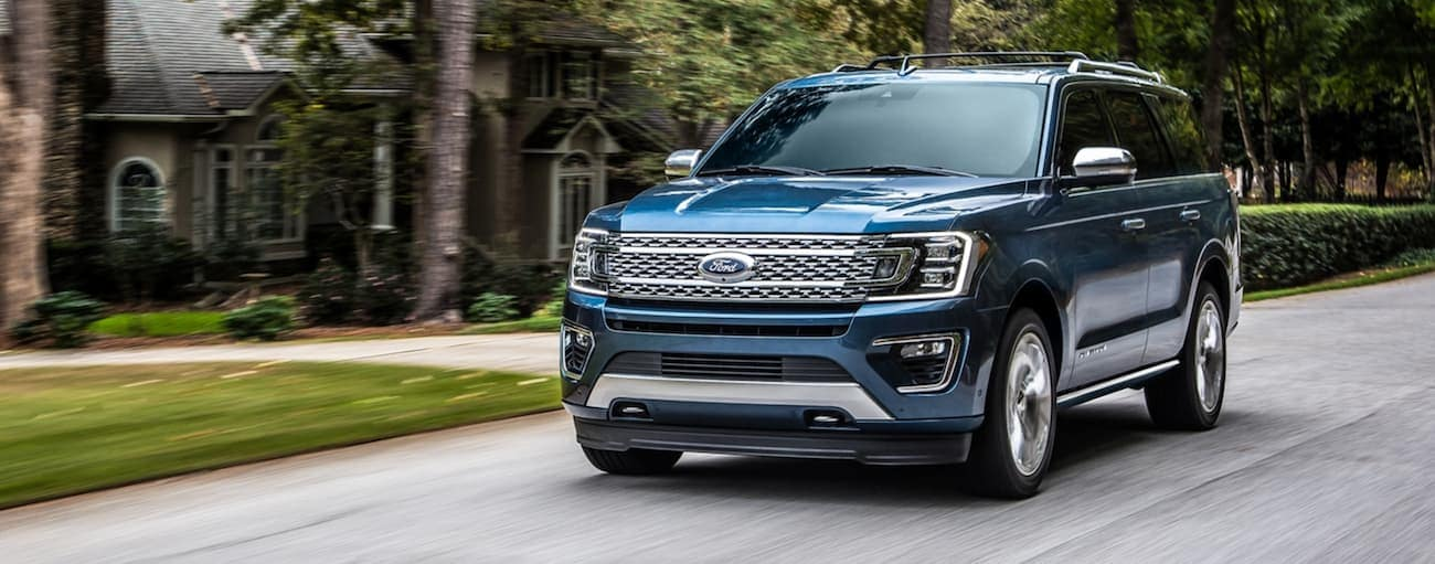 A blue 2020 Ford Expedition is driving through a neighborhood near Cincinnati, OH, after winning the 2020 Ford Expedition vs 2020 Nissan Armada comparison.
