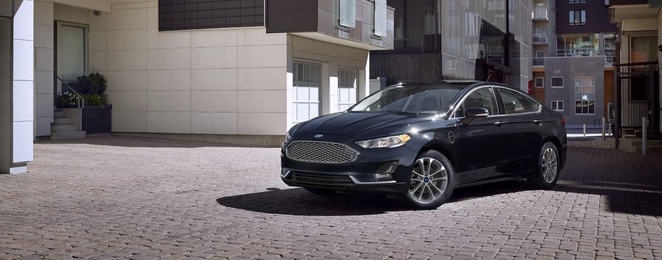 A black 2020 Ford Fusion Hybrid is parked on a side street in front of townhouses.