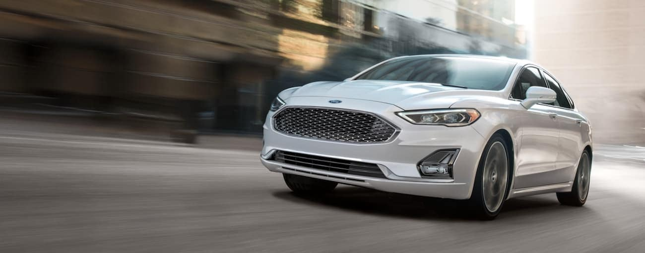 A white 2020 Ford Fusion is driving on a Cincinnati, OH, street after winning the 2020 Ford Fusion vs 2020 Chevy Malibu comparison.
