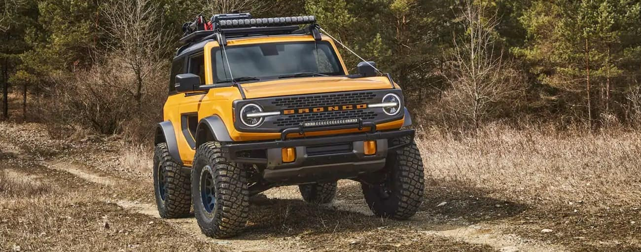 A yellow 2021 Ford Bronco 2-Door is off-roading on a dirt trail outside of Cincinnati, OH.