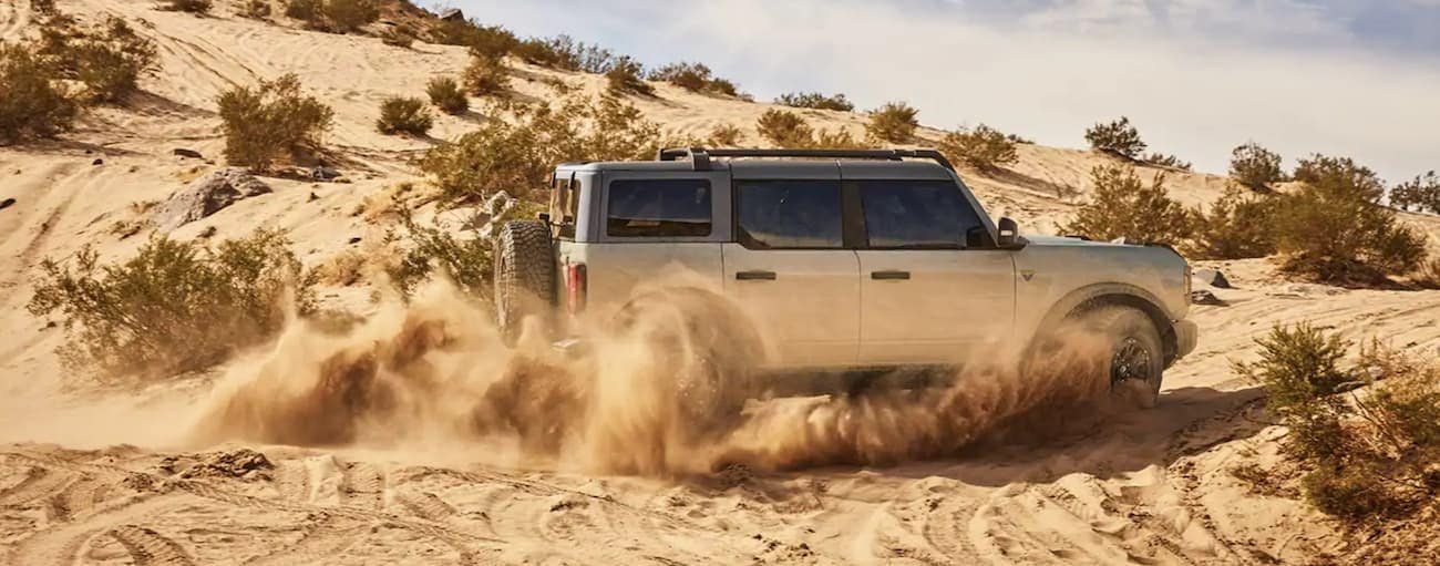 A blue 2021 Ford Bronco 4-Door is driving through loose sand in the desert.