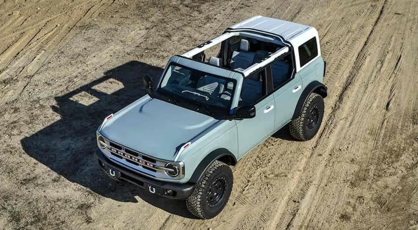 A blue 2021 Ford Bronco is shown from an above angle on dirt.