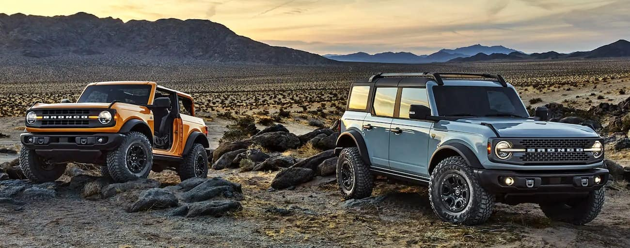 A yellow 2-Door and a blue 4-Door Ford Bronco are parked in the desert in front of mountains.