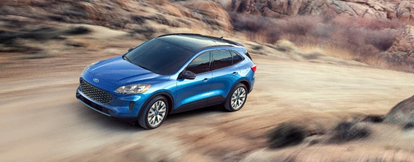 A blue 2020 Ford Edge is driving on a dirt trail and shown from a high angle.