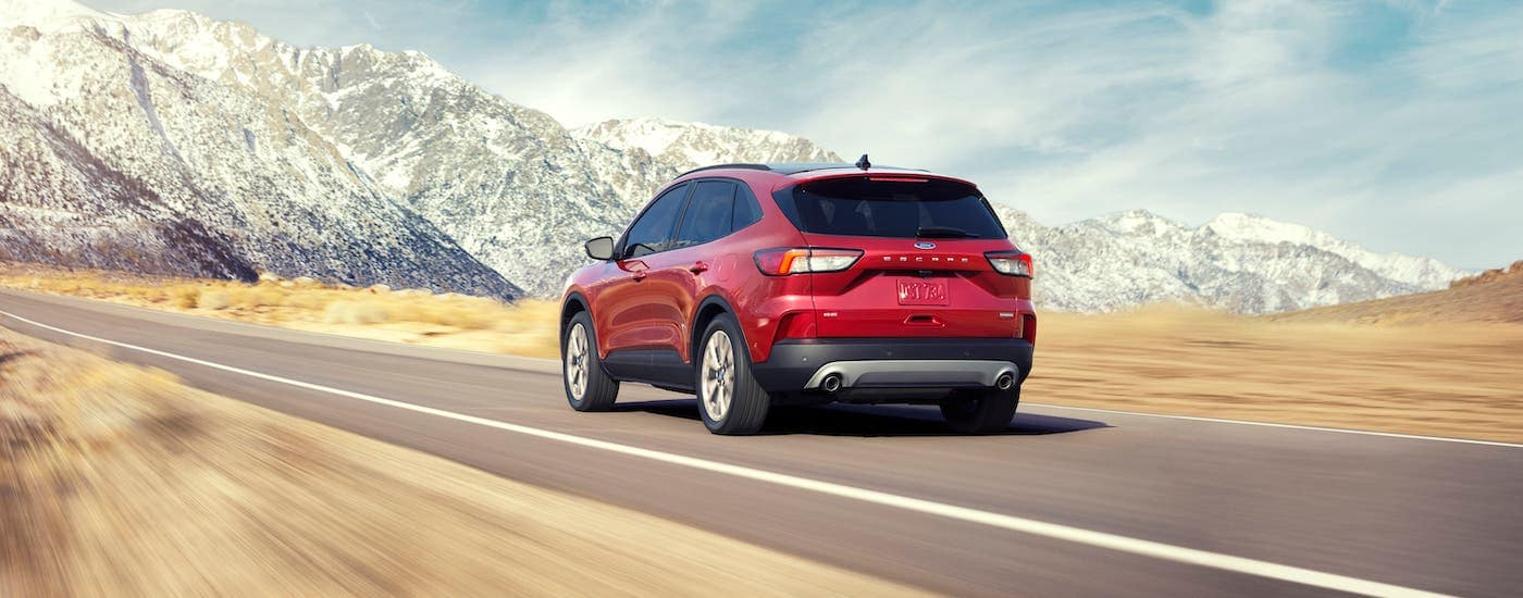 Is this the best SUV? A red 2020 Ford Escape is shown driving away on a highway towards mountains.