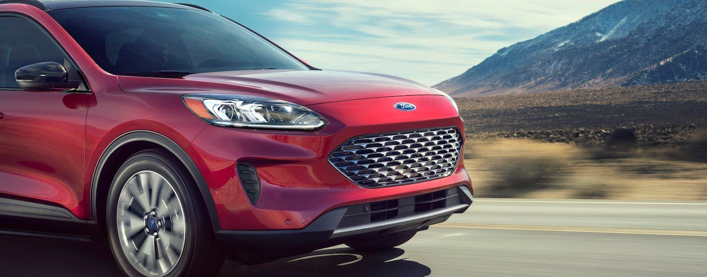 The grille and front of a red 2020 Ford Escape is shown driving on a highway.