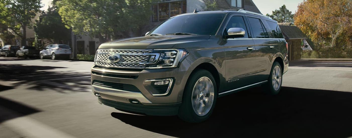 A gray 2020 Ford Expedition Platinum is driving on a suburban road.
