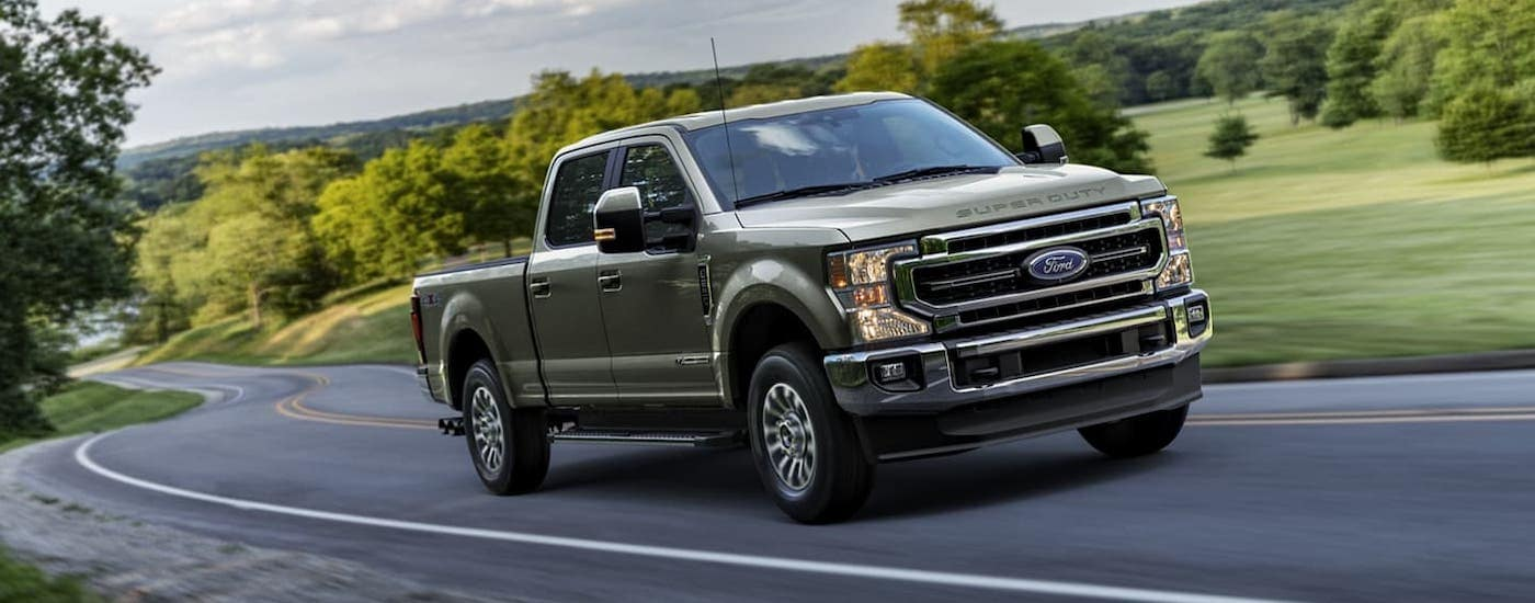 A gray 2020 Ford F-250 is driving on a rural road.