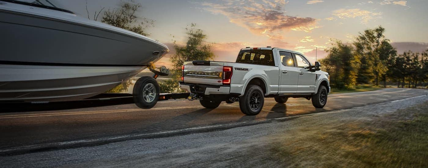 A white 2020 Ford F-250 is towing a boat at sunset on a highway near Cincinnati, OH, after winning the 2020 Ford F-250 vs 2020 Chevy Silverado 2500HD comparison.