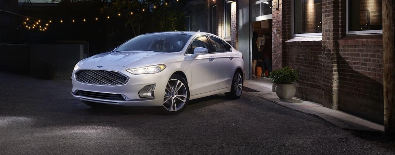 A white 2020 Ford Fusion is parked on a city street at night in Cincinnati, OH. after winning the 2020 Ford Fusion vs 2020 Subaru Legacy comparison.