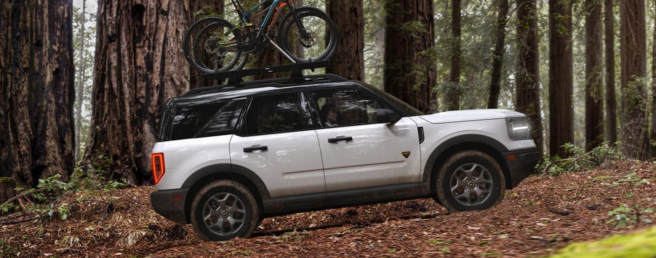 A white 2021 Ford Bronco Sport is shown from the side off-roading in the woods with bikes on the roof.