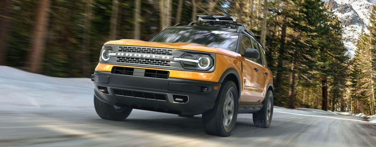 A yellow 2021 Ford Bronco Sport is driving on a snow-lined road past large trees.