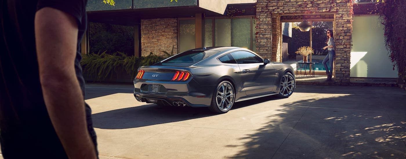 A man is walking towards a gray 2020 Ford Mustang parked in front of a modern home and a woman leaning against a wall. Find your next Ford in Cincinnati at Kings Ford.
