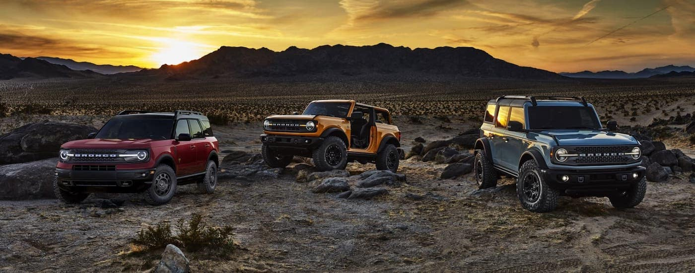 A red 2021 Ford Bronco Sport and an orange 2021 Ford Bronco 2-door and blue 4-door are parked on rocks in front of a desert sunset.