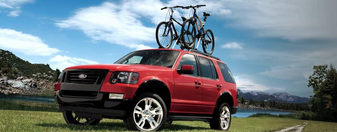A red 2009 used Ford Explorer with bikes on the roof is driving on a dirt road.