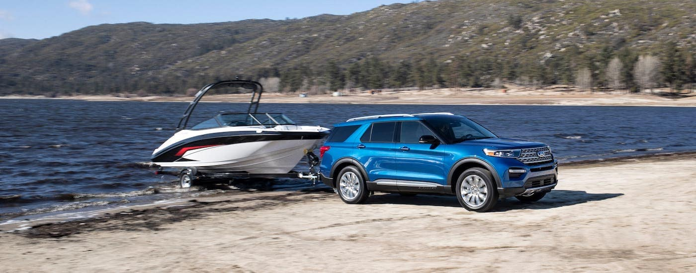 A blue 2020 used Ford Explorer Hybrid is towing a boat out of a lake.