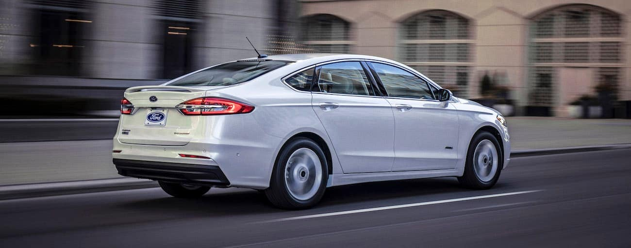 A white 2020 Ford Fusion is driving away on a city street near Cincinnati, OH.