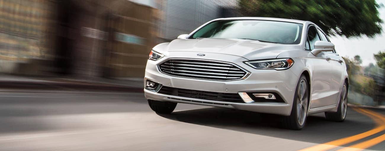 A white 2020 Ford Fusion is driving on a city street after winning the 2020 Ford Fusion vs 2020 Mazda6 comparison.
