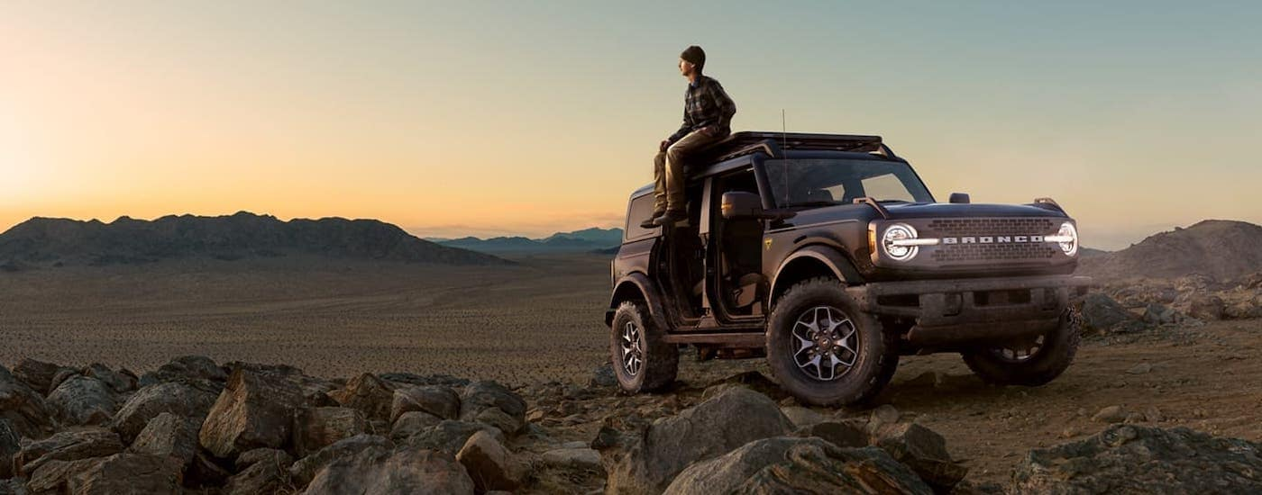 A man is sitting on the roof of a gray 2021 Ford Bronco four-door with no doors and overlooking a desert.