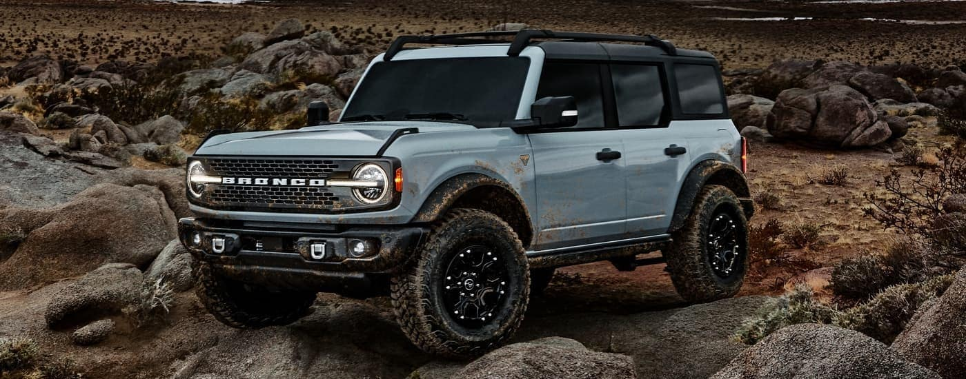 A light blue 2021 Ford Bronco four-door is crawling over rocks as part of the 2021 Ford Bronco vs 2021 Ford Bronco Sport comparison.