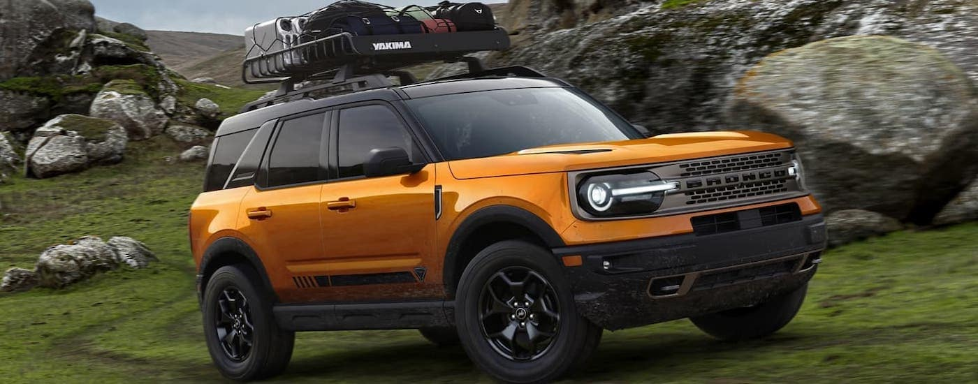 An orange 2021 Ford Bronco Sport, coming to your local Cincinnati Ford dealer, with luggage on the roof is driving around large rocks.