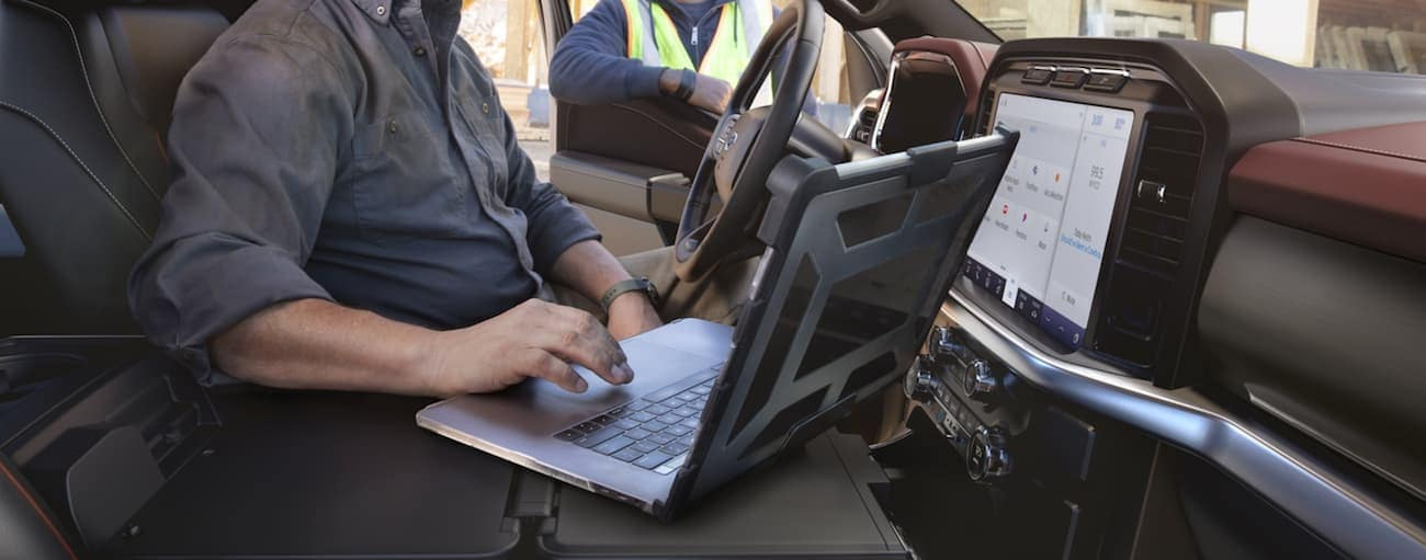 A man is in a 2021 Ford F-150 on a laptop while talking to a construction worker outside the truck.