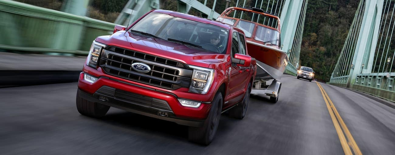 A red 2021 Ford F-150 is towing a boat across a bridge near Cincinnati, OH, after winning the 2021 Ford F-150 vs 2020 Ford F-150 comparison.