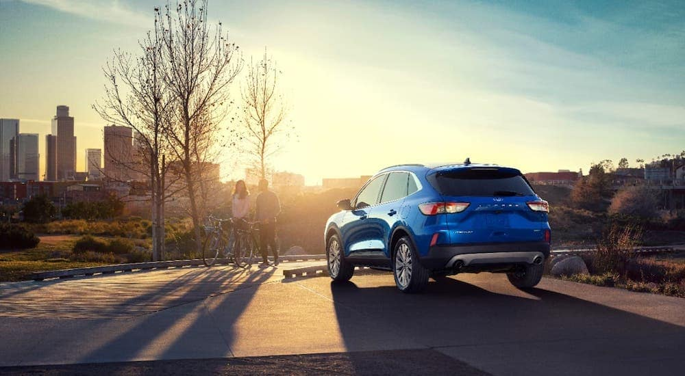 A blue 2020 Ford Escape from a local Ford dealership is overlooking a city sunset.