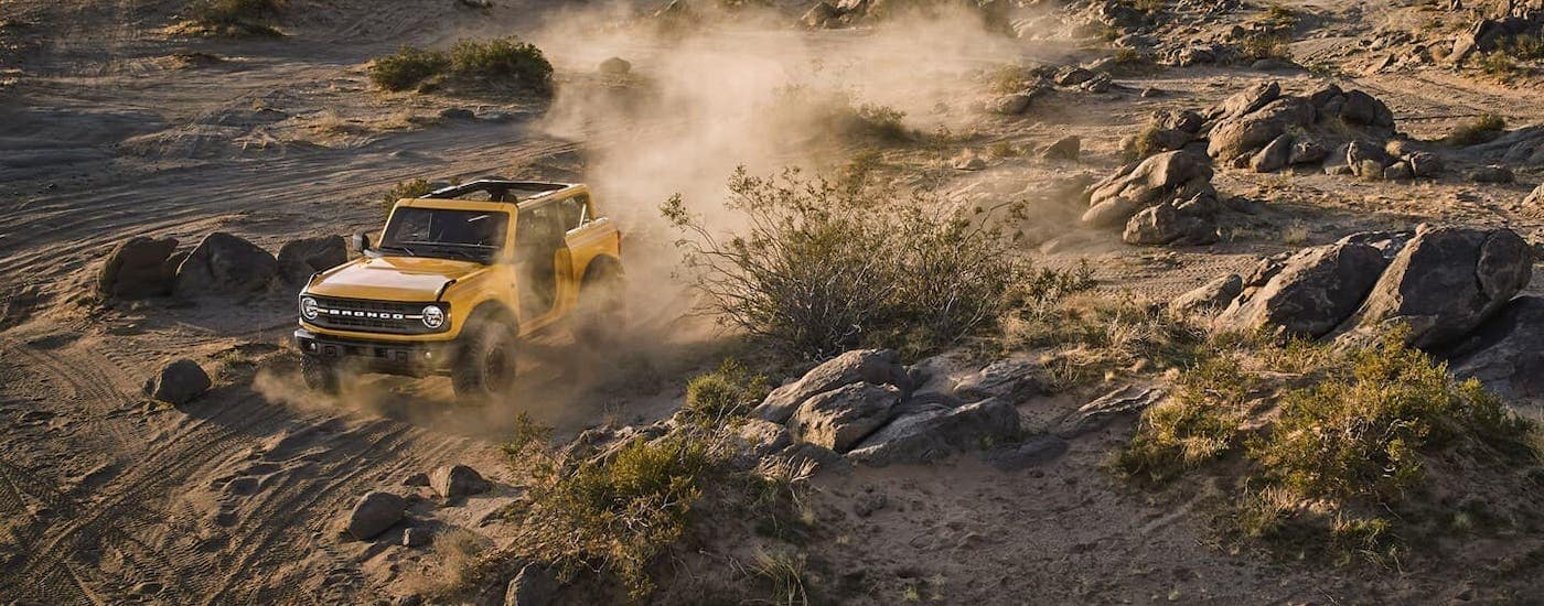 A yellow 2021 Ford Bronco 2-door is driving on a dirt field.