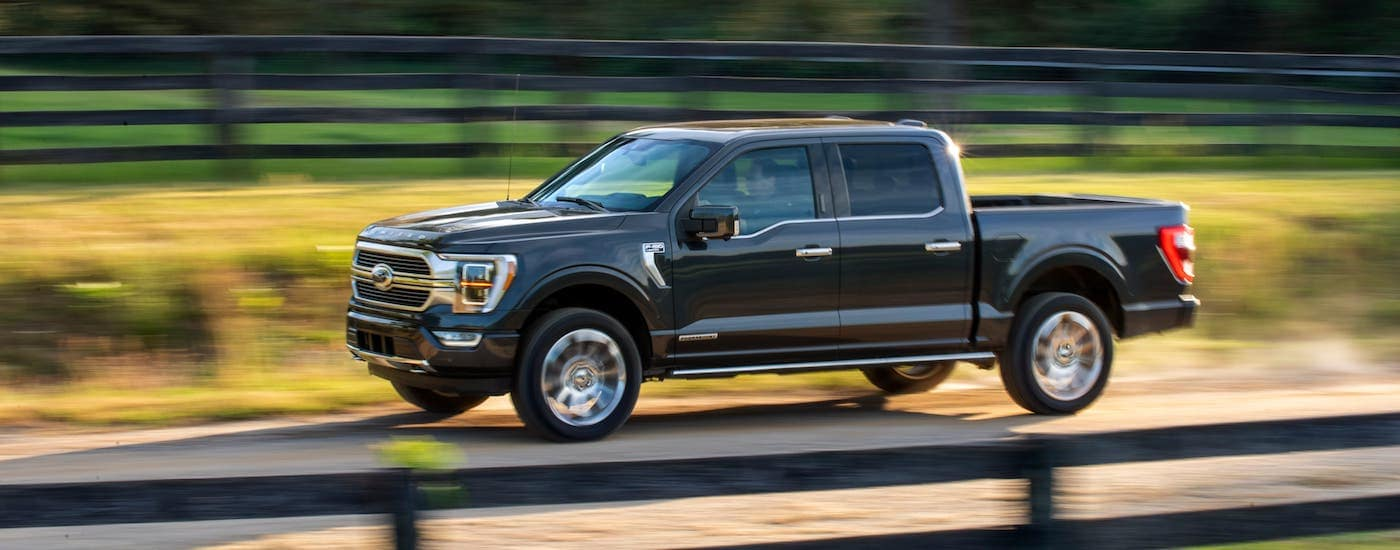 A black 2021 Ford F-150 Hybrid is driving past fenced in fields outside of Cincinnati, OH.