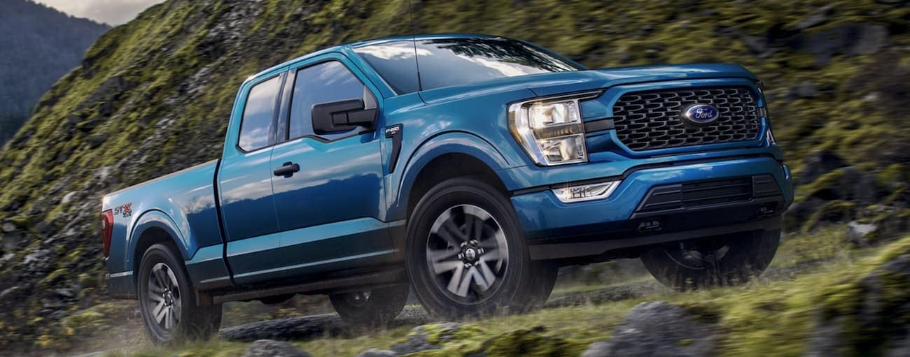 A blue 2021 Ford F-150, a popular Ford truck for sale, is off-roading up a mountain trail.