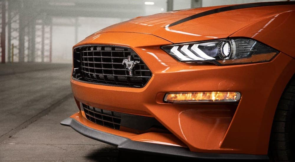 A closeup shows the grille of an orange 2020 Ford Mustang grill.