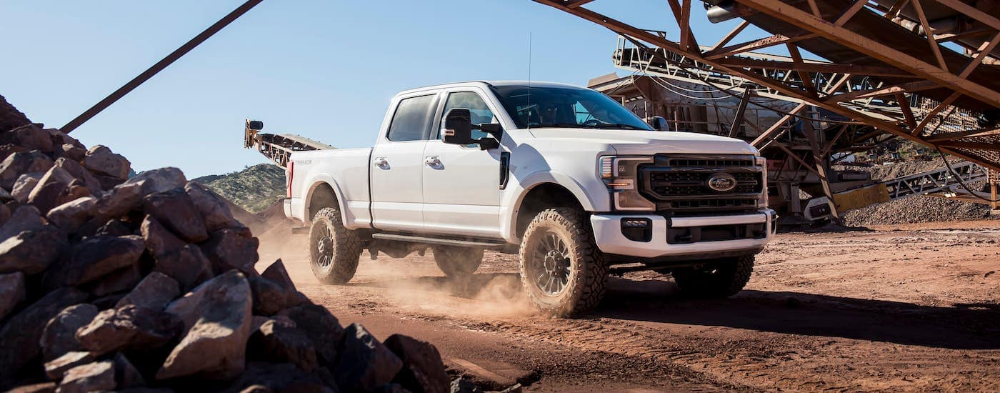 A white 2020 Ford F-250 Lariat Sport Tremor is is driving through a gravel pit after winning the 2020 Ford F-250 vs 2020 GMC Sierra 2500 comparison.