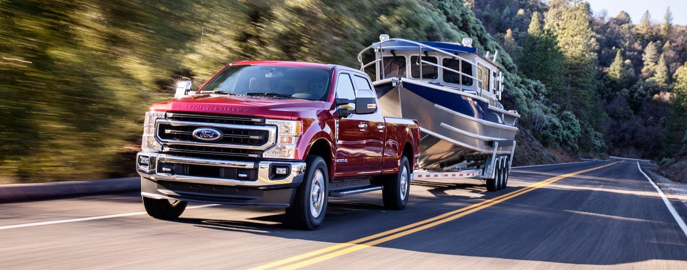A red 2020 Ford F-250 is towing a boat on a highway near Cincinnati, OH.