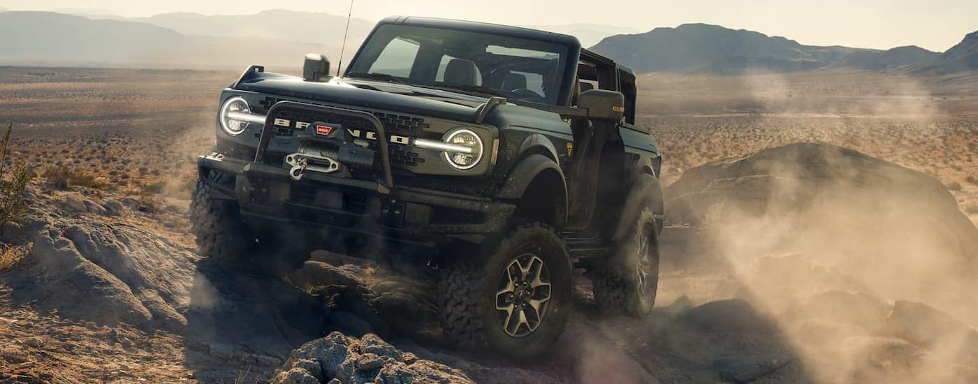 A black 2021 Ford Bronco 2-door with no roof or doors is off-roading in a desert as part of the 2021 Ford Bronco (2dr) vs 2020 Jeep Wrangler (2dr) comparison.