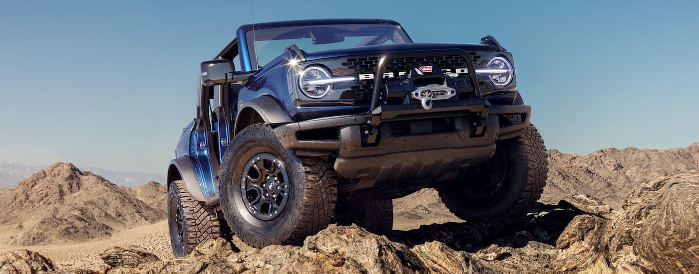 A blue 2021 Ford Bronco 4-door with no roof or doors is climbing over rocks as part of the 2021 Ford Bronco (4dr) vs 2020 Jeep Wrangler Unlimited comparison.