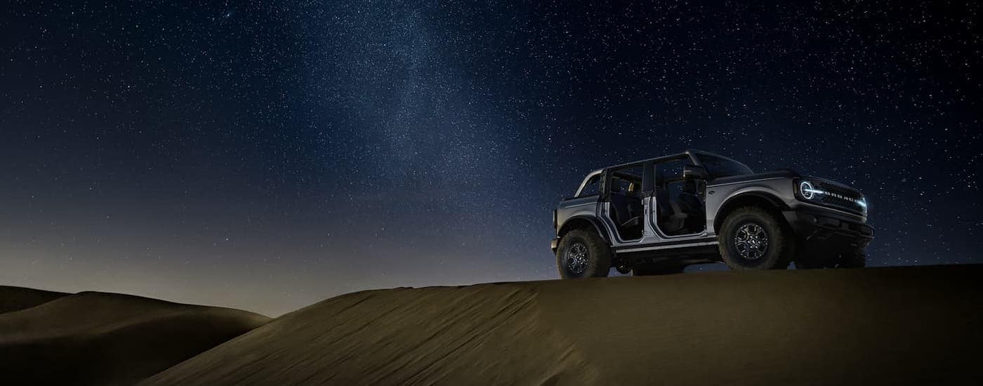 A silver 2021 Ford Bronco 4-door with no roof or doors is parked on a sand dune against a starry sky.