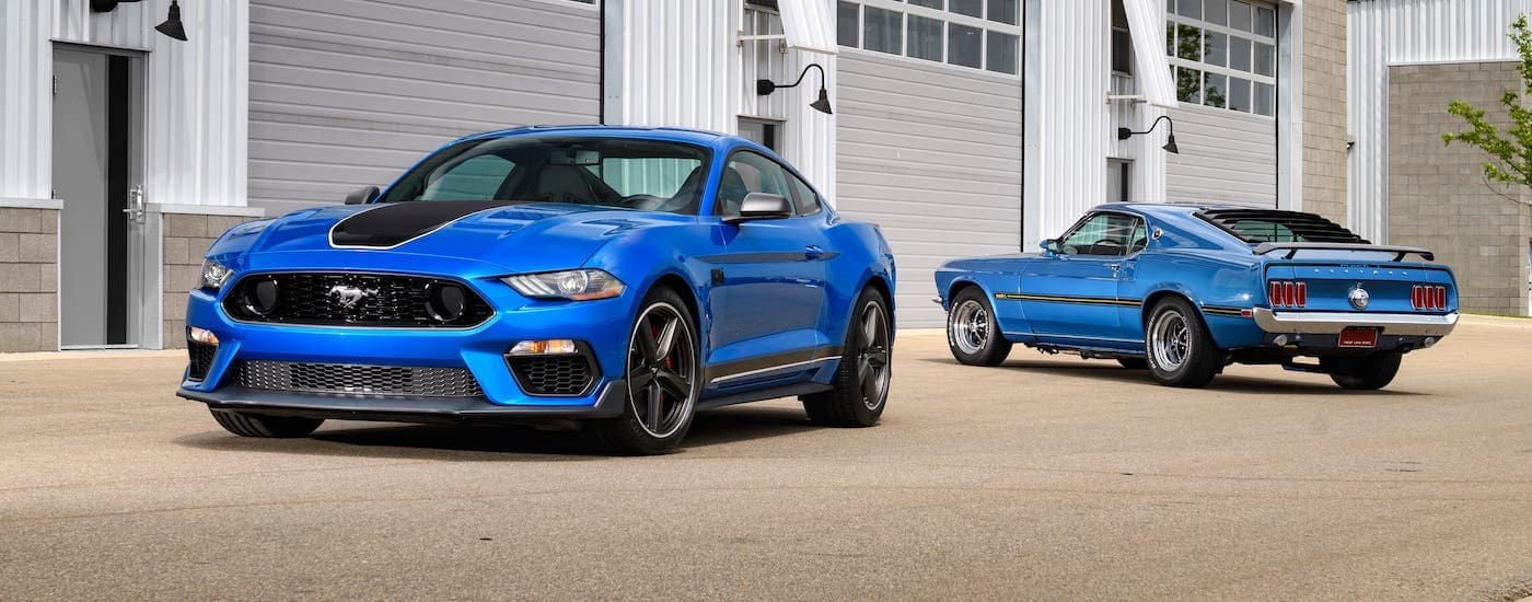 A blue 2021 Ford Mustang Mach 1 and a blue 1970s Mustang Mach 1 are parked in front of a garage.