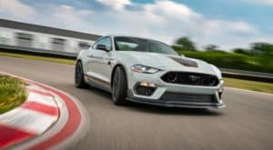 A white 2021 Ford Mustang Mach 1 is driving around a corner on a track near Cincinnati, OH.