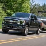 A black 2021 Ford F-150 from a local Ford dealership is towing a boat on a highway near Cincinnati.